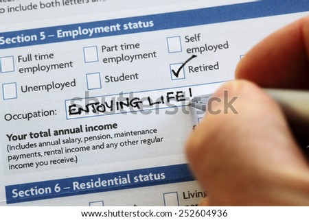 Writing retired and enjoying life on an application form concept for a comfortable retirement - stock photo