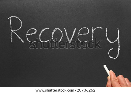 Writing the word recovery on a blackboard.