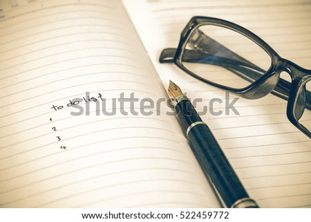 writing to do list on notebook page with pen on wood background