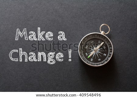 Written Make A Change ! words on black background with compass - stock photo