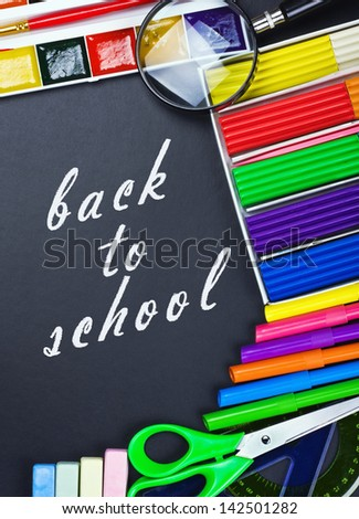 written on the blackboard back to school and supplies for school - stock photo