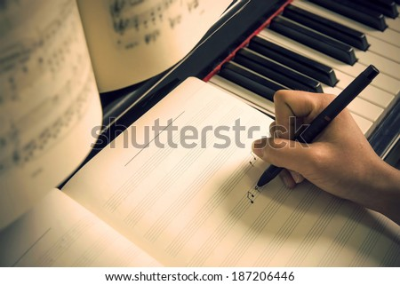Written on the piano sheet music - stock photo