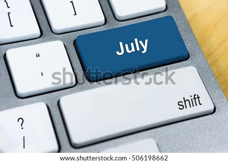Written word July on blue keyboard button. Monthy Online Planning Management Concept