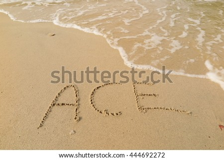 "written words ""ACE"" on sand of beach"