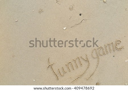 "written words ""funny game"" on sand of beach"
