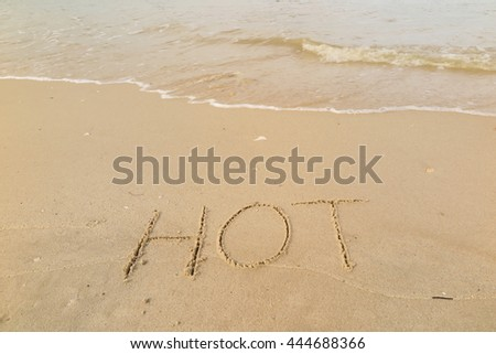 "written words ""HOT"" on sand of beach"