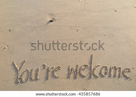 "written words ""You're welcome"" on sand of beach"