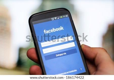 WROCLAW, POLAND - APRIL 05, 2014: Hand holding smartphone with Facebook social network mobile app with polish interface