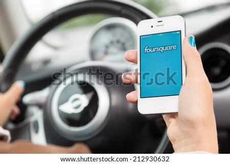 WROCLAW, POLAND - AUGUST 05, 2014: Photo of a young woman sitting in a Mini Cooper car holding an iPhone 4 smartphone device - stock photo