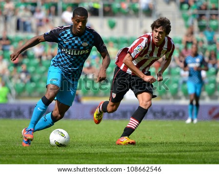 WROCLAW, POLAND - JULY 21: Semifinal Polish Masters tournament match PSV Eindhoven and Athletic Bilbao, Georginio Wijnaldum (L) and  Ander Iturraspe (R) in action on July 21, 2012 in Wroclaw, Poland. - stock photo