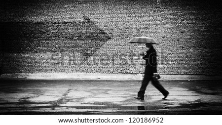 Wrong way. A man with umbrella. Conceptual image, film grain added - stock photo