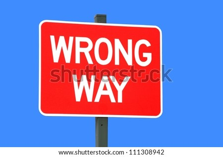 wrong way sign isolated against a blue background - stock photo