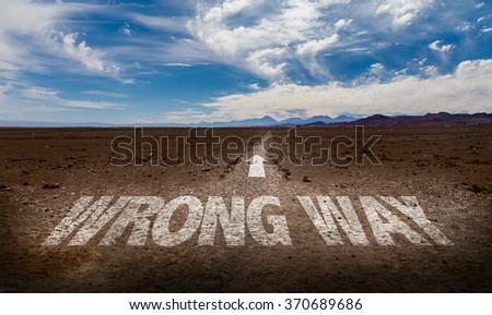Wrong Way written on desert road - stock photo