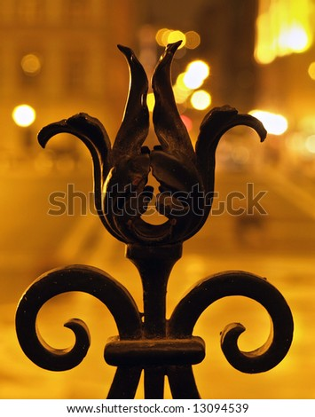 Wrought iron fence detail at night - stock photo