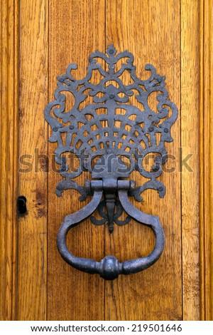 Wrought iron knocker on a sturdy oak timber door - stock photo