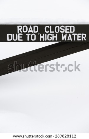 "Wry wintry humor: Deep snow lies piled above wooden barrier with notice that reads, ""Road closed due to high water"""