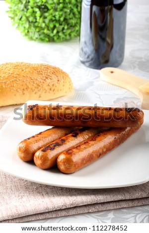 Wurstel on dish on complex background - stock photo