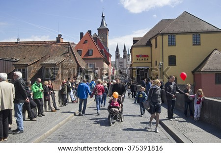 Wurzburg, Germany - May 4, 2014: People cross the old Main Bridge across the Main river in Wurzburg, Germany on May 4, 2014 - stock photo