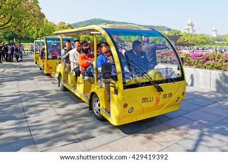 WUXI, CHINA - April 18, 2016: At Ling Shan the electric tour cars are bringing tourists from the entrance to the very footsteps of the great Buddha statue. - stock photo