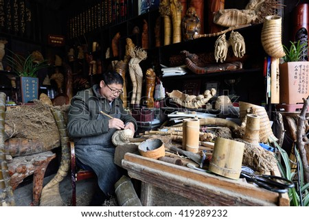 WUZHEN, CHINA - MARCH 24: Unidentified chinese craftsman making traditional souvenirs on March 24, 2016 in Wuzhen, China. Wuzhen is a historic scenic town, located in northern Zhejiang Province, China - stock photo