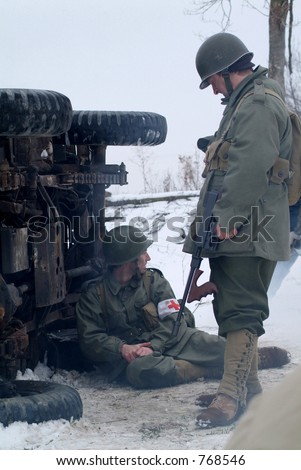 WWII Soldiers in a winter setting. (next to an over turned jeep)