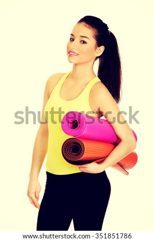 Wxercise fitness woman ready for workout with yoga mats. - stock photo