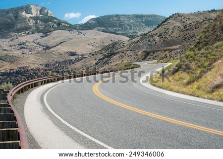 Wyoming Mountain Road:  A curving road climbs through the mountains of Bighorn National Forest in northeast Wyoming.  - stock photo