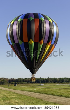 X Marks the Spot.  Colorful hot air balloon dips low to ground to drop beanbag directly on target. - stock photo