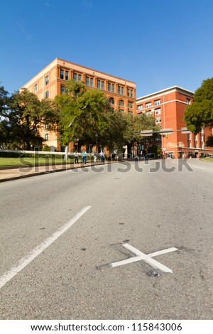 X on the road where President John F. Kennedy was assassinated with the Book Depository in the background - stock photo