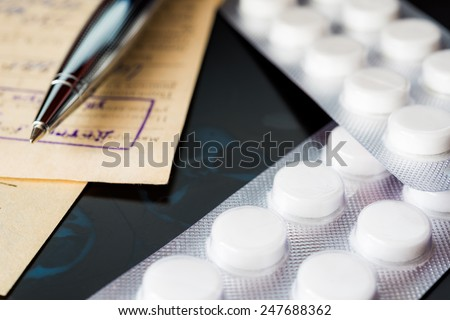 X-ray examination, a prescription and tablets for treatment of disease, a pen on the recipe. Focus on the pills - stock photo