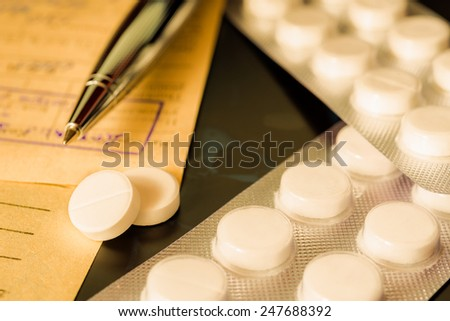 X-ray examination, a prescription and tablets for treatment of disease, a pen on the recipe. Focus on the pills, in yellow tones - stock photo