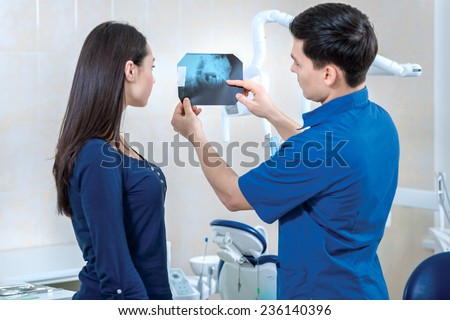 X-ray picture of teeth. Successful doctor takes the patient's dentist and dental x-ray shows in his medical dental office. Doctor wearing medical clothing. People are looking at the camera - stock photo