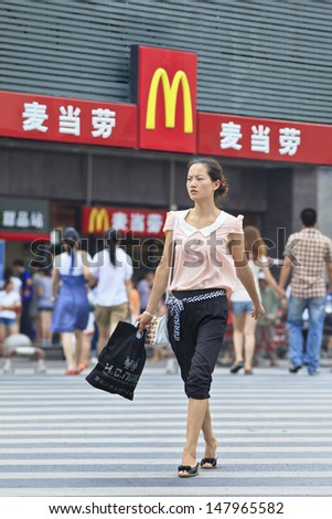 XIANG YANG-CHINA-JULY 3. Charming girl walks in front of McDonald. It took McDonald 19 years to reach 1,000 restaurants in China, it plans to raise it to 2,000 this year. Xiang Yang, July 3, 2012 - stock photo