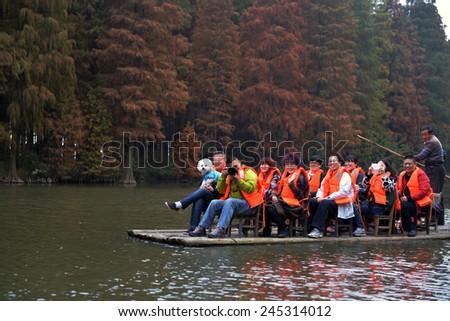 XINGHUA,CHINA - NOVEMBER 22, 2014: Tourists view the Li Zhong water forest, not far from Taizhou, on a raft made of bamboo shoots. - stock photo