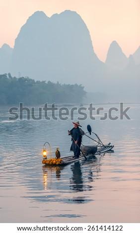 XINGPING, CHINA - OCTOBER 24, 2014: Fisherman stands on traditional bamboo boats at sunrise - The Li River, Xingping, China - stock photo