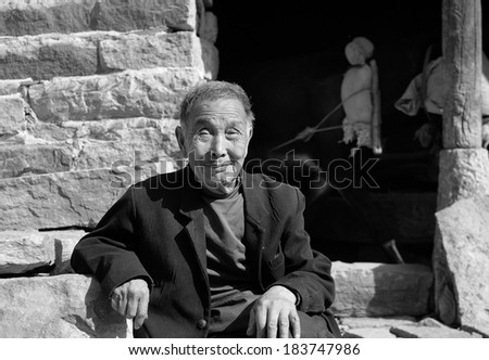 XINGTAI CITY, CHINA - OCT 2012: On October 11, 2012, Wang Nao village of Xingtai City, an unidentified old man sitting on a stone in the sun.