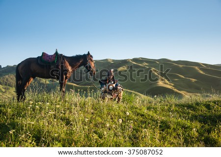 Xinjiang, China - 2012 July 29 : A lonely mongolian warrior take a rest with their horse on a grasslands after riding a horse for 4 hours to ride across the biggest grassland in China