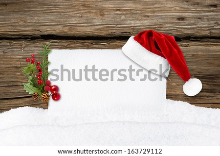 xmas card with santa hat in front of wooden background - stock photo