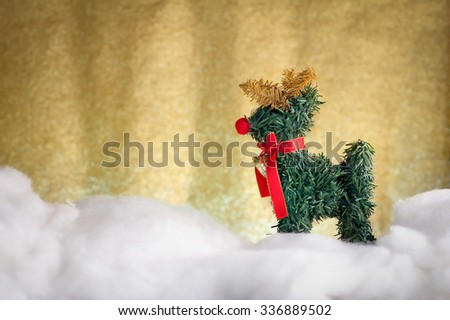 xmas deer Christmas decoration in snow with gold glitter background.jpg - stock photo