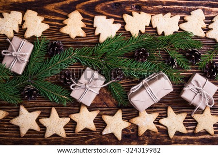 Xmas holiday background with spruce twigs, gift boxes, christmas tree and star shaped cookies, top view, selective focus - stock photo