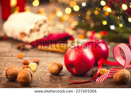 Xmas holiday table setting, decorated with garlands, baubles, walnuts, hazelnuts, cinnamon sticks. Christmas Stollen. Traditional Sweet Fruit Loaf with Icing Sugar.  Warm colors toned.  - stock photo