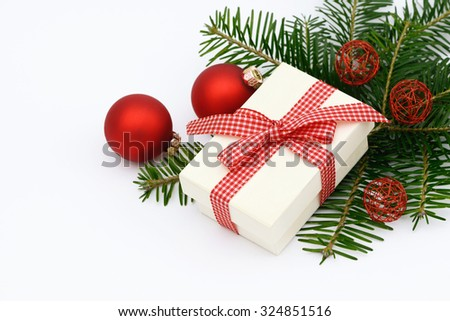 Xmas present and xmas bauble lying on fir  - stock photo