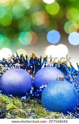 Xmas still life - blue balls, tinsel at green tree with blurred green and blue Christmas lights background - stock photo