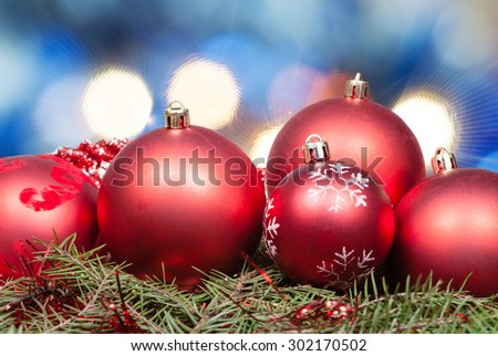 Xmas still life - red balls at green tree with blurred blue Christmas lights background - stock photo
