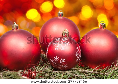 Xmas still life - red balls at green tree with blurred orange, yellow, red Christmas lights background - stock photo