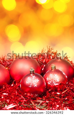 Xmas still life - red baubles, tinsel with blurred yellow Christmas lights bokeh background