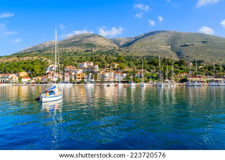 Yacht boat on blue sea and view of Agia Efimia fishing village with port, Kefalonia island, Greece - stock photo