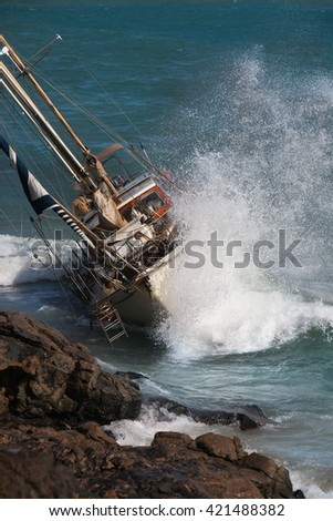 yacht crash on the rocks after stormy weather - stock photo