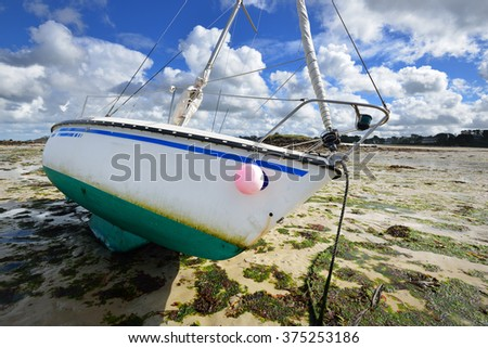 Yacht during ocean low tide in Plouguerneau, Brittany, France - stock photo