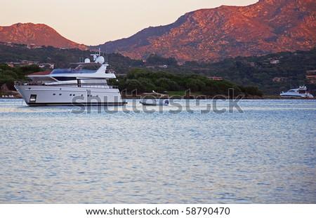 Yacht in Sardinia at sunset. - stock photo